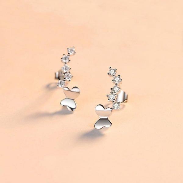 пълзящи по ухото сребърни обеци с кристали и елемент под формата на пеперуда снимани на светъл фон