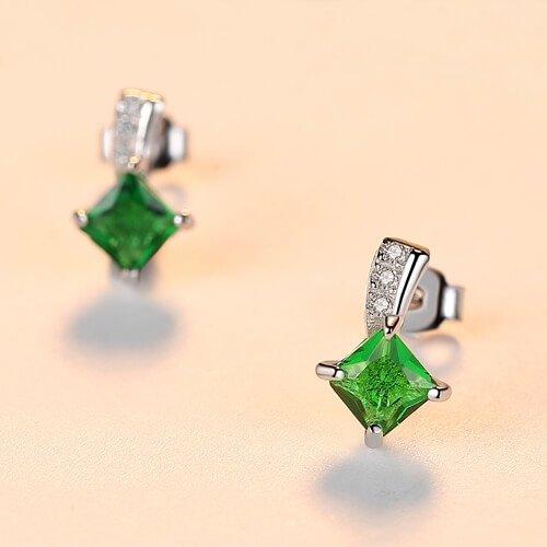 детайлна снимка на сребърни обеци на винт с яркозелен кристал