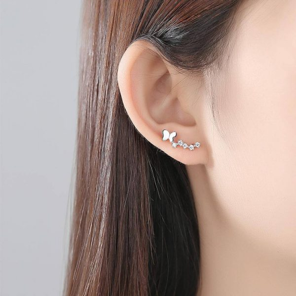 дамско ухо с пълзящи по ухото сребърни обеци с кристали и елемент под формата на пеперуда
