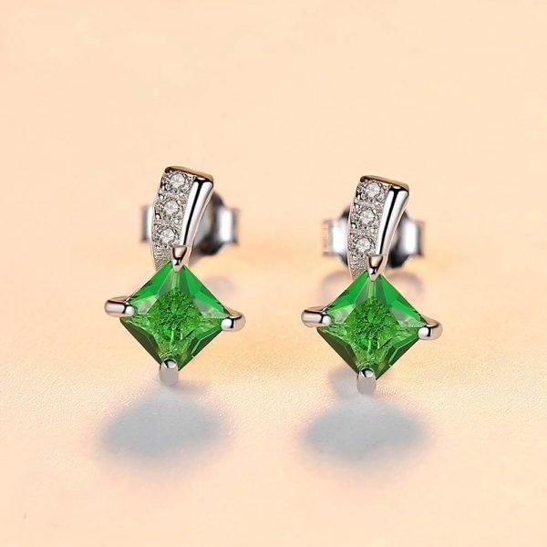 сребърни обеци на винт с яркозелен кристал снимани фронтално на светъл фон