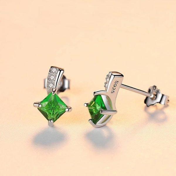 сребърни обеци на винт с яркозелен кристал снимани под лек ъгъл